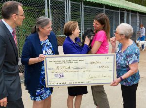 "Savarese presents a donation from Cape Cod Five's foundation to the MSPCA pet adoption center in Falmouth, Mass. ""Whether it's through our banking, through our corporate leadership and volunteerism, our financial education, our philanthropy, or even our business practices, we feel that everything we have to do has to contribute to the vitality of our community,"" she says."